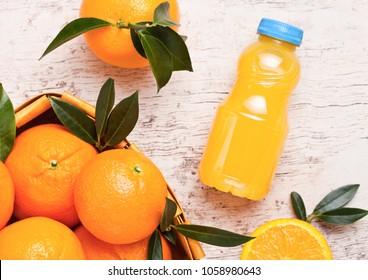 Plastic mini bottle of organic fresh orange juice with raw oranges in bamboo box on wooden background