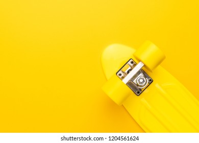 plastic mini cruiser board on yellow background. bright yellow cruiser skateboard with copy space