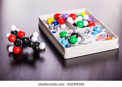a plastic molecule structure modeling kit on a wooden surface