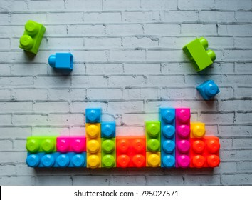 Plastic multicolored building blocks on white background with text space.