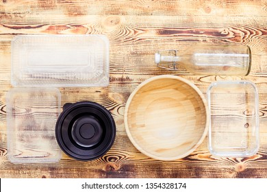 Plastic and natural dishes on wooden background