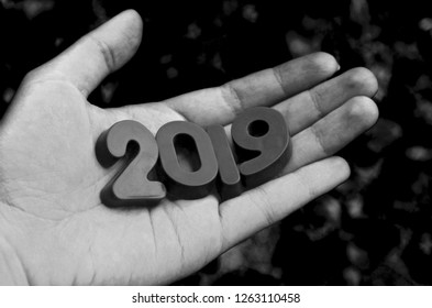 Plastic numbers 2019 year in open palm. Black 2019 numbers in hand close up. Loss and regret concept. Sad mood and nostalgia. Remember this year. Sad events. Prediction and forecast. Fortune telling.