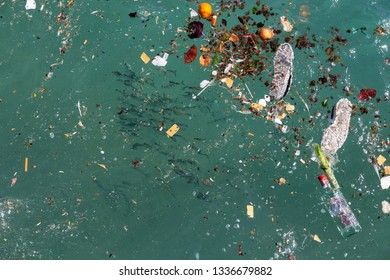 Plastic in ocean. Shoal of fish and plastics and trash in sea.