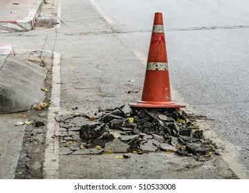 Plastic orange cone on the damaged asphalt road