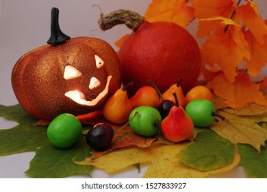 """A plastic orange pumpkin with a """"sinister"""" grimace and a candle (multi-colored LEDs) inside, driving away evil spirits from the house.  Pumpkin with plastic fruits on autumn maple leaves."""