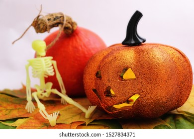 """A plastic orange pumpkin with a """"sinister"""" grimace and a candle (multi-colored LEDs) inside, driving away evil spirits from the house.  Pumpkin on maple leaves. Plastic human skeleton."""