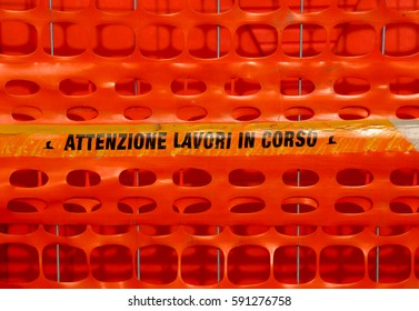 Plastic orange safety net to delimit the area of a road construction site with ITALIAN words meaning CAUTION WORK IN PROGRESS