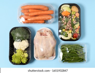 Plastic packages of chicken and vegetables on blue background