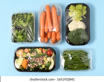 Plastic packages with vegetables on blue background