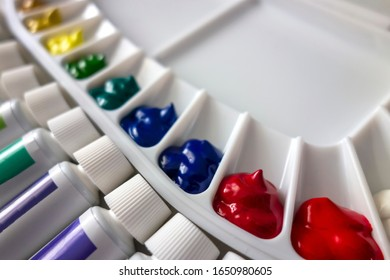 A plastic palette filled with watercolor with paint tubes.