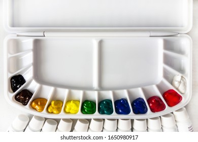 A plastic palette filled with watercolor with paint tube caps visible.