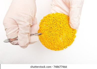 Plastic pellets . Colorant for polymers in granules. Plastic pellets in the hands with gloves and tweezers . Polymer granules