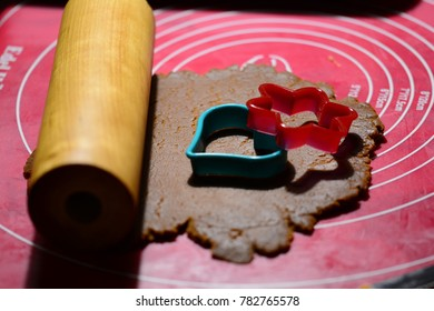 Plastic pink and green heart and star shaped gingerbread forms on top of gingerbread dough. Pink background. Wooden rolling pin. Baking home made gingerbread cookies around Christmas time in Winter