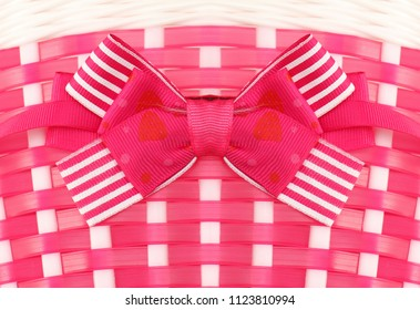 Plastic pink knited background with decorative bow attached to the front