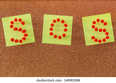 Plastic pins form into S.O.S. on blank notepads