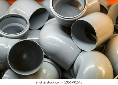 Plastic pipe bends in a pile. Industrial products for construction.