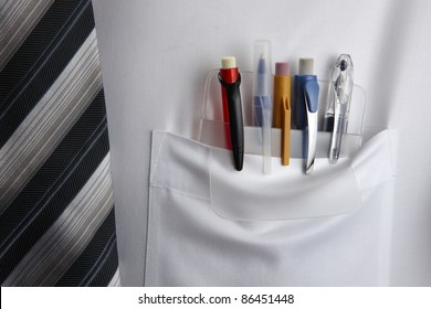Plastic pocket protector holding pens and pencils in white shirt