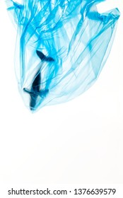 Plastic pollution creative concept advertise for campaign save oceans and earth by photo of humpback whale model struck in blue plastic bag with copy space. Plastic looks transparent by studio light.