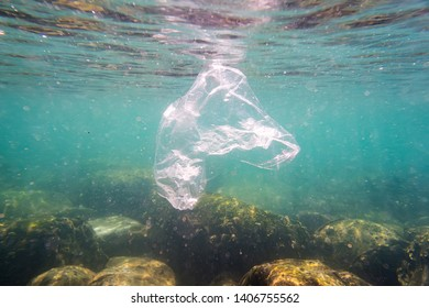 Plastic pollution: discarded plastic rubbish bag floats on tropical coral reef presenting a hazard to marine life