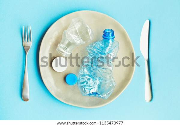 plastic pollution of food concept, handmade plate with plastic bottles and caps on blue background