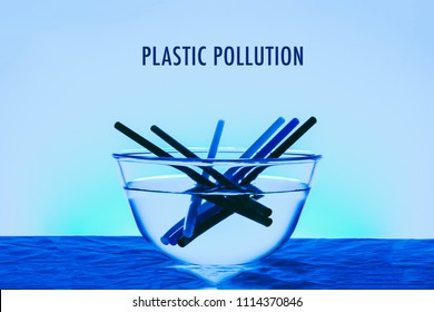 Plastic pollution title in the ocean concept photo with glass of bowl and plastic straw blue color effect