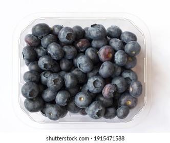 Plastic punnet full of lush blueberries against plain white background