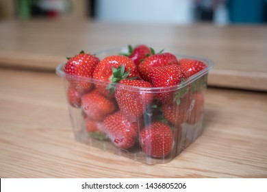 Plastic punnet of strawberries on a wooden table. Close up and blurred background. Delicious fresh red fruits. Not eco-friendly. Recycling must be done with this plastic container (supermarket).