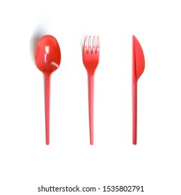 Plastic red disposable spoon, fork and knife. Close up. Isolated on white background.