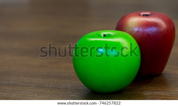 plastic red and green apple were on the wooden table