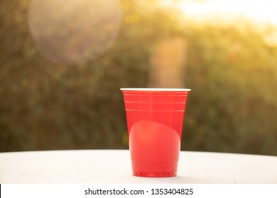 Plastic red solo drinking cup for beer pong or drinking games with green background on a white table.