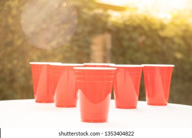 Plastic red solo drinking cups for beer pong or drinking games with green background on a white table.