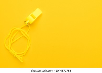 plastic referee whistle on the yellow background with copy space