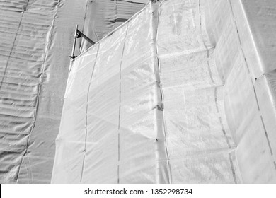 Plastic safety net and scaffolding around a building which is restored in black & white.