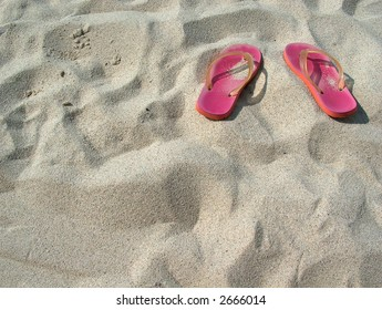 plastic sandals on a sandy beach