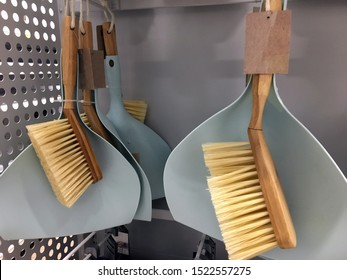 Plastic scoops with brushes on a store's sail. Scoops and brushes. Small wooden sweeping brush. Close-up of a sweeping brush. Sold at the store. Stand with brushes for sweeping the floors in the store