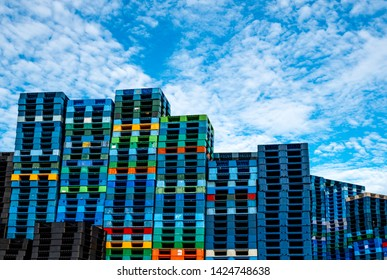 Plastic shipping pallet for sale and for rent business. Industry plastic pallet stacked at factory warehouse. Cargo and shipping business concept. Pile of plastic pallet for distribution and delivery.