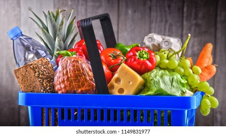 Plastic shopping basket with assorted grocery products.
