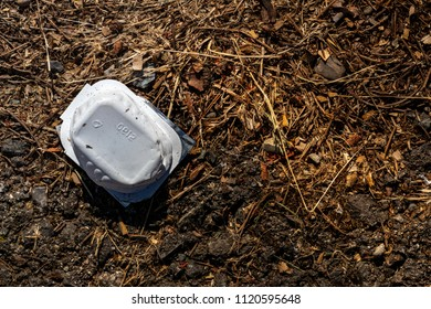 Plastic single use dipping sauce container trash tossed on the ground