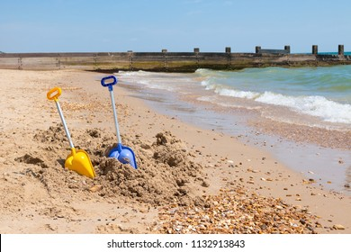 Plastic spade scoops left in the sand on the beach