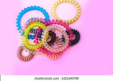 Plastic spiral colored colorful scrunchies for women hairdressing hairstyle on pink background with free copy space for text