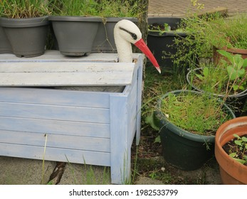 a plastic stork hiddne in a wooden box between some pot plants
