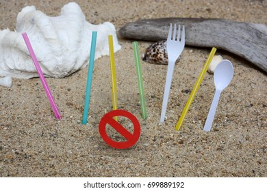 Plastic straw and fork with stop sign on sandy beach background with seashell and driftwood. Ban single use plastic. Environmental concept.