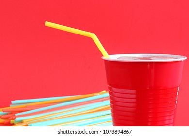 Plastic straw on red background.  World leaders around the world are pushing to ban disposable straws
