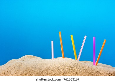 Plastic straw on sandy beach with blue background.  Pollution from these plastic items left on beach hurts sea creatures and harmful to marine ecology. Pollution concept. Ban single use plastic.