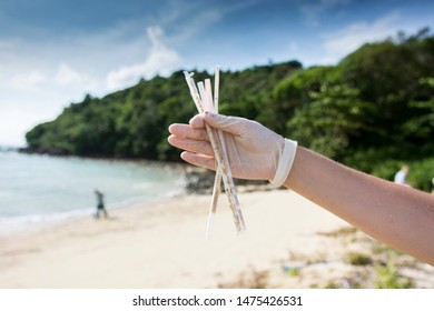 plastic straw pollution, Hand in a plastic glove holding plastic straws after a beach clean up