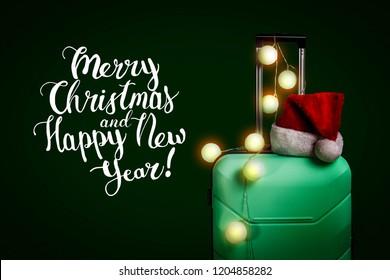 Plastic suitcase, Santa Claus hat and garland on dark blue backg