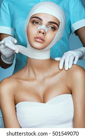 Plastic Surgeon bandaging head of young beautiful woman. Photo of Beautiful Woman after Plastic Surgery Operation.