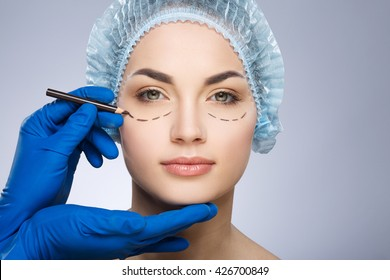 Plastic surgeon drawing dashed lines under eyes of girl. Hands in blue glove holding pencil and face. Girl in protective cap. Plastic surgery, beauty portrait