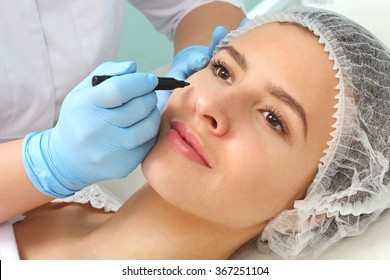 Plastic surgeon drawing lines over eyelid of a nice young female before cosmetic operation.