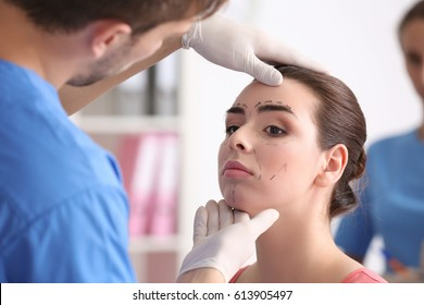 Plastic surgeon examining young woman's face prior to operation in clinic